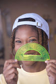 African American woman with protractor in front of face — Stock Photo