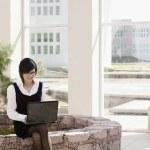Hispanic businesswoman using laptop outdoors — Stock Photo #23330944