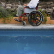 Senior man using laptop in wheelchair — Stock Photo