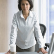 Eurasian businesswoman looking stern in office — Stock Photo