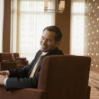 Businessman smiling in lobby — Stock Photo