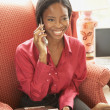 African businesswoman talking on cell phone in armchair — Foto de Stock