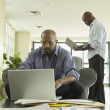 African businessmen working on laptops in office — Stock Photo