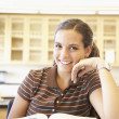 Teenaged girl with text book in classroom — Stock Photo