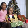 African girl giving grandmother Christmas gift — Stock Photo