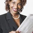 Mixed race businesswoman holding newspaper — Stock Photo