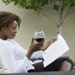 African woman reading on patio and drinking red wine — Stock Photo
