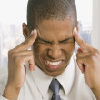 Mixed race businessman with headache — Stock Photo