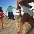Multi-ethnic group of friends running on beach — Stok fotoğraf