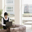 Hispanic businesswoman using laptop outdoors — Stock Photo #23330944