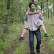 Asian man giving girlfriend piggy back ride in forest — Stock Photo