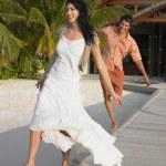 Couple walking on beach boardwalk — Stock Photo
