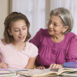 Hispanic grandmother helping granddaughter with homework — Stok fotoğraf