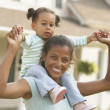 African mother holding daughter on shoulders — Stock Photo