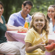 Hispanic family eating at picnic table — Stock Photo #23331100