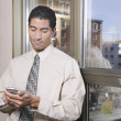 Mixed race businessman text messaging on cell phone — Stock Photo