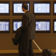 Hispanic businessman looking at flight information monitors — Photo