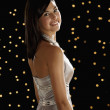 Hispanic woman smiling in evening gown with lights in background — Stock Photo
