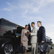 Multi-ethnic businesspeople next to limousine — Stock Photo
