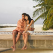 Couple sitting on beach boardwalk — Stock Photo