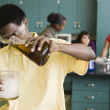 African teenage boy performing experiment in chemistry lab — Stock Photo