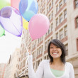 Asian woman holding bunch of balloons — Stock Photo