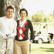 Couple next to tree with golf clubs — Stock Photo