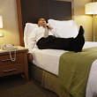 Middle-aged businessman laying on bed in hotel room — Stock Photo