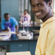 African teenage boy studying in chemistry lab — Stock Photo #23331436