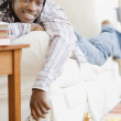 African man watching television on sofa — Stock Photo