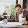 Businessman reading newspaper at cafe — Foto Stock