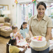 Hispanic mother holding cake at daughter's birthday party — Stock Photo #23331532