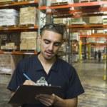 Hispanic man writing on clipboard in warehouse — Stock Photo