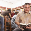 Teenaged Hispanic boy smiling with book in library — Stok fotoğraf