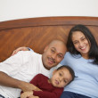 Boy lounging in bed with parents — Stok fotoğraf