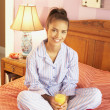 Royalty-Free Stock Photo: Hispanic woman in pajamas holding orange juice