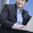 Asian businessman working on laptop outdoors — Stock Photo