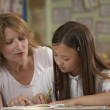 Teacher helping student at desk — Stockfoto