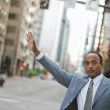 African businessman hailing a taxi — Stock Photo