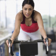 Hispanic woman riding stationary bicycle — Stock Photo