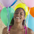 African woman holding bunch of balloons and laughing — Stock Photo