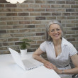 Portrait of senior woman next to laptop — Stock Photo