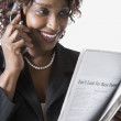 Mixed race businesswoman talking on cell phone and reading newspaper — Stock Photo