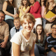 Teenaged girl smiling in front of group of students — Photo