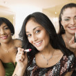 Hispanic woman applying makeup in bathroom — Stock Photo #23331906
