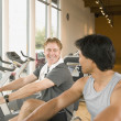 Two men using exercise bikes in health club — Stock Photo #23331944