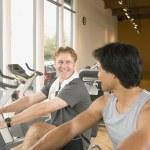 Two men using exercise bikes in health club — Stock Photo
