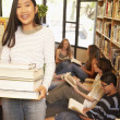 Teenagers with books in library — Stok fotoğraf