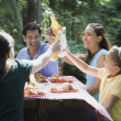 Hispanic family toasting at picnic table — Stock Photo