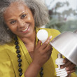 African woman changing lightbulb at home — Stock Photo
